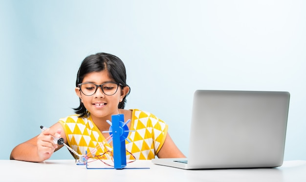 Электронный эксперимент - азиатская индийская студентка, выполняющая исследование ветряной мельницы с помощью проводов, соединений, учится с ноутбука или планшета.