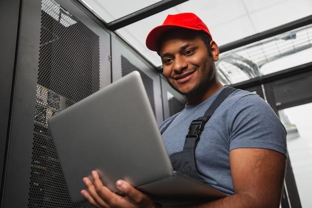電子フレームワーク。笑顔でノートパソコンを運ぶ陽気なitエンジニアのローアングル
