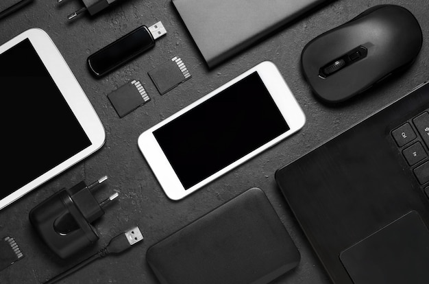 Electronic gadgets on a black concrete background. concept of accessories for successful business. flat lay.