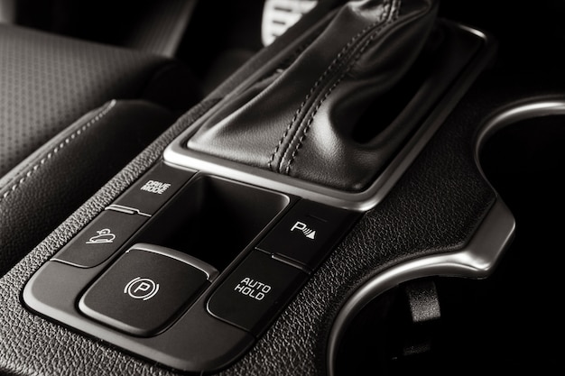 Electronic handbrake button on a new car with luxurious and modern details