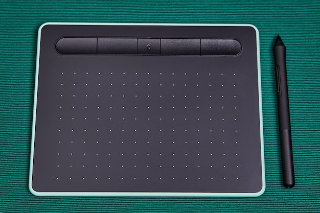 An electronic input device for personal computer, graphic tablet with a stylus pen, lies on table.
