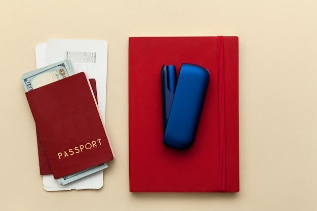 ベージュの背景に飛行機のチケットとお金が付いた電子iqosタバコの赤い日記パスポート