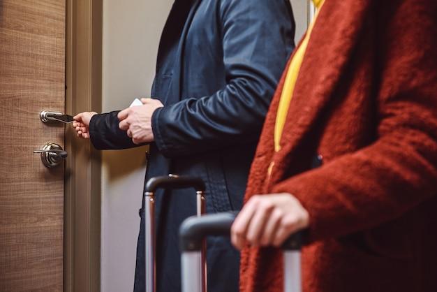 ホテルの部屋からの電子キー。近くの若いカップルが荷物を持ってホテルの部屋に入り、おしゃべりをしている。閉じる