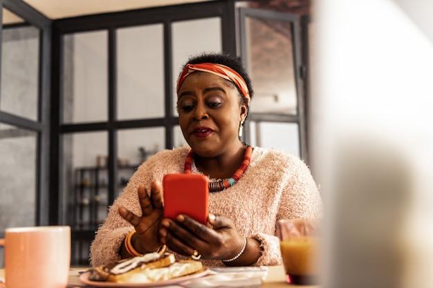 전자 우편. 그녀의 사서함을 확인하는 동안 그녀의 스마트 폰을 사용하는 행복 즐거운 여자