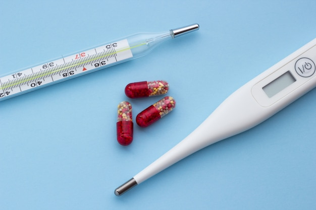 Electronic and mercury thermometer with red-yellow pills on a blue background