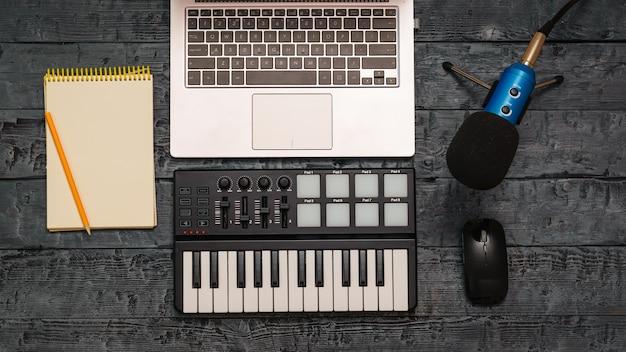 Смеситель электронной музыки, компьтер-книжка, карандаш и проводной микрофон на черном деревянном столе. оборудование для музыкальной студии. вид сверху.