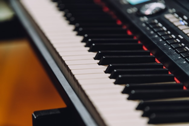Electronic musical keyboard synthesizer with white and black keys in recording studio