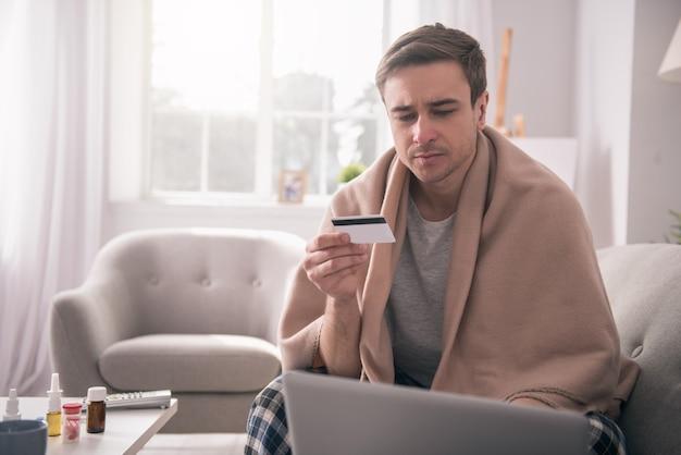 電子決済。彼の手でクレジットカードを保持しながらノートパソコンの画面を見ている悲しい病気の男
