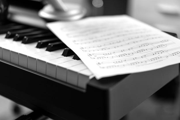 전자 피아노와 악보. 흑백 사진, 음악적 배경