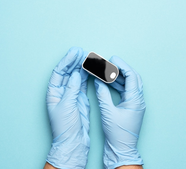 Electronic pulse oximeter in the hands of a doctor, wearing blue latex gloves, close up