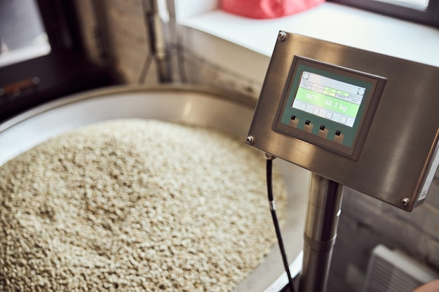 Electronic scales with numbers on screen and green coffee beans in hopper on blurred background