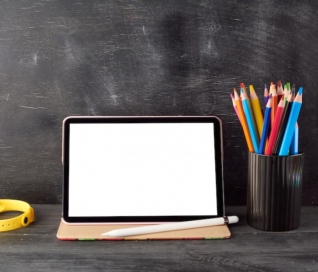 Electronic tablet with a blank white screen and multi colored wooden pencils