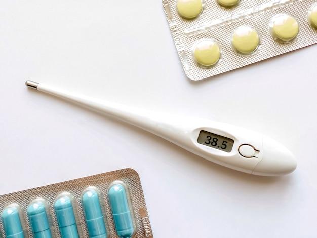 전자 온도계 및 흰색 배경에 알 약입니다. 의학 및 건강 개념입니다. 바이러스 질병의 치료입니다.
