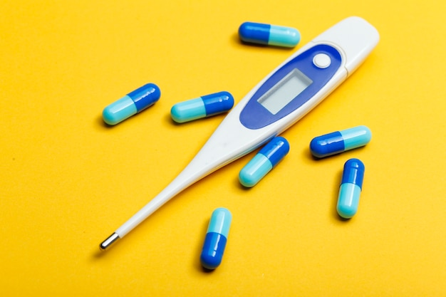 Electronic thermometer and blue capsules on yellow background