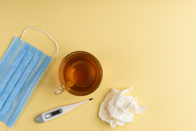 Electronic thermometer, cup of tea, mask and green pills on yellow background.