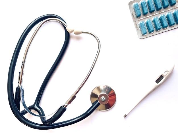 전자 온도계, 안압계 및 흰색 배경에 알 약입니다. 의학 및 건강 개념입니다. 의료 템플릿입니다.