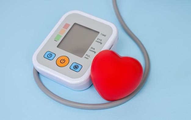 赤い心臓のクローズアップで血圧を測定するための電子眼圧計