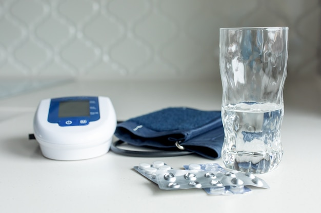 Electronic tonometer, pills and a glass of water on a white table