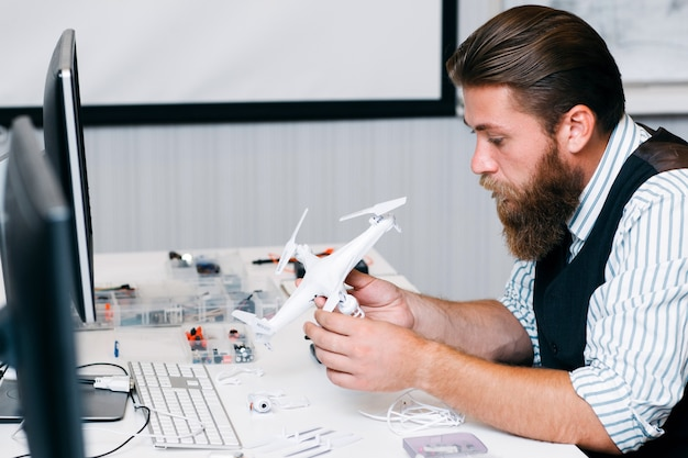 Electronic toy repair shop,. bearded master disassembling broken hexacopter for renovation. business, occupation, technology concept