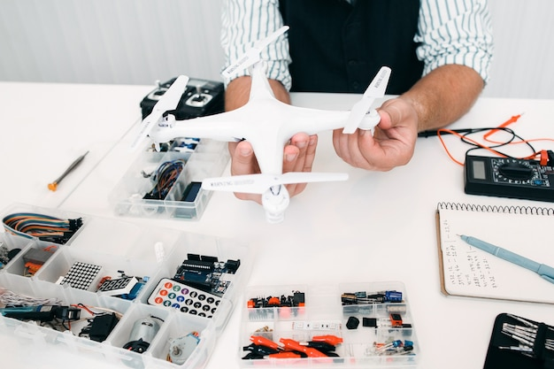 ドローンのある電子玩具修理店。専門家による改修中の壊れた航空機。電子固定、技術、革新の概念