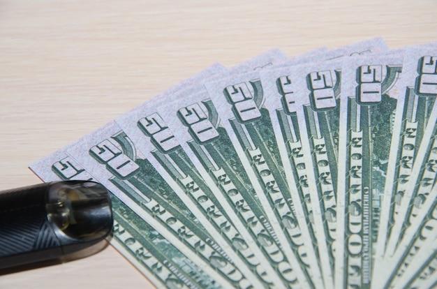 Electronic vape pen on top of 50 dollar bills