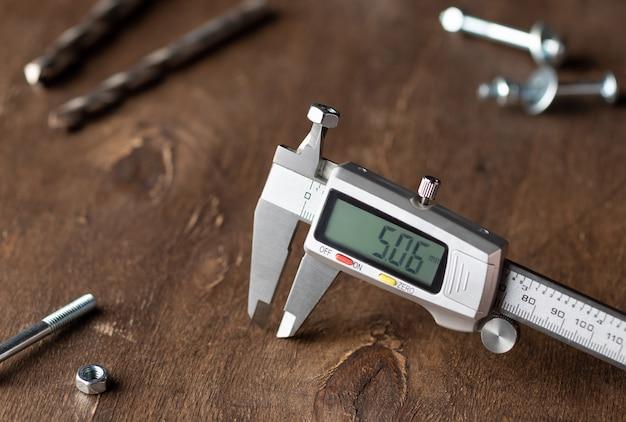 Электронный штангенциркуль на деревянных фоне