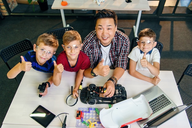 무선 제어 자동차 모델과 함께 작업하는 젊은 유럽 학생들과 전자 엔지니어 교사. 전선 및 회로 납땜, 물리적 실험.