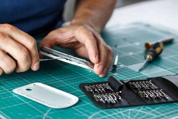 전자 제품 수리 서비스. 검사를 위해 기술자가 스마트 폰을 분해합니다.