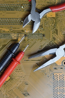 The electronics repair tool lies on the motherboard from the computer. close-up.