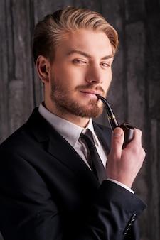 エレガンスと男らしさ。パイプを吸ってカメラに笑顔の正装でハンサムな若い男の肖像画