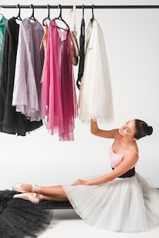 Elegance ballerina sitting on mobile clothes rack looking at tutu