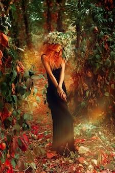 屋外の頭にホップの花輪と森でポーズをとる優雅な美しさの女性