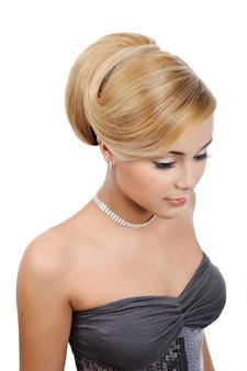 モダンな光沢の髪型を持つ優雅な金髪の若い女性