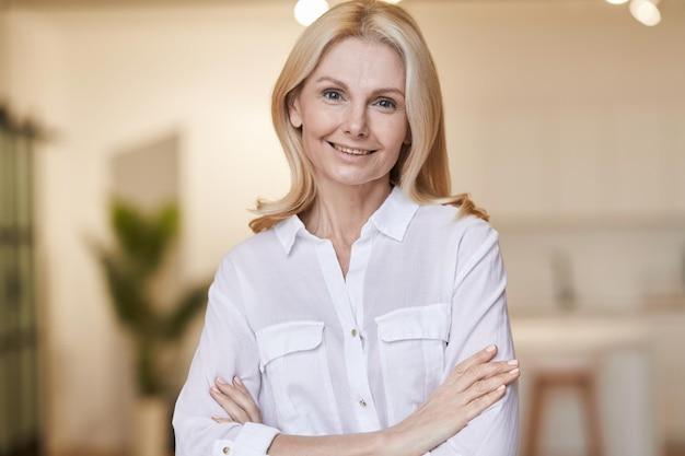 실내에서 포즈를 취하는 동안 카메라를 보며 웃고 있는 흰 셔츠를 입은 친절한 성숙한 여성의 우아한 초상화
