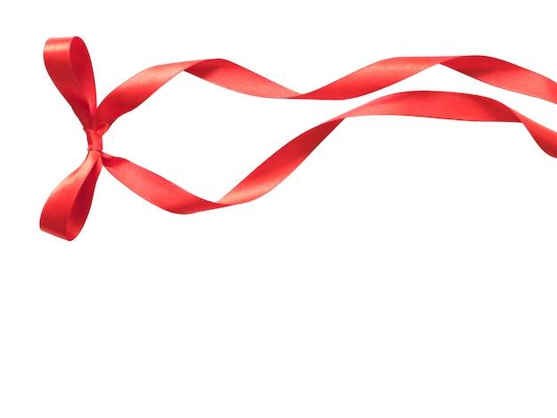 コピースペースで白に分離されたエレガンスな赤いリボン