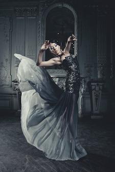 Женщина элегантности с платьем летания в комнате дворца