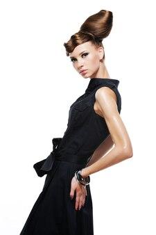 Элегантная стильная гламурная девушка в модном черном платье, изолированном на белом
