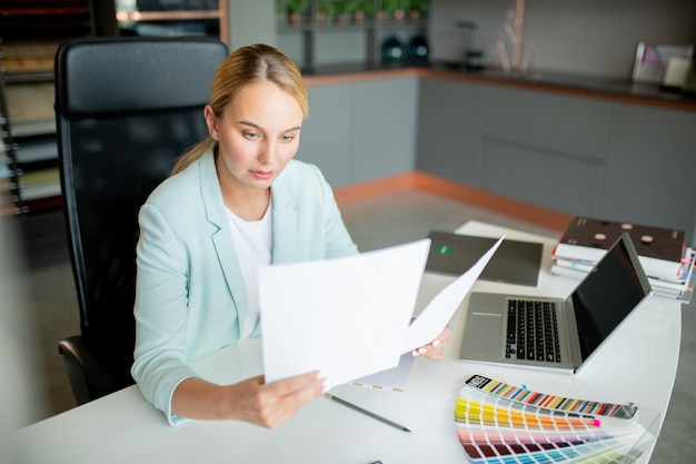 Elegant accountant or broker looking through financial papers while working in office