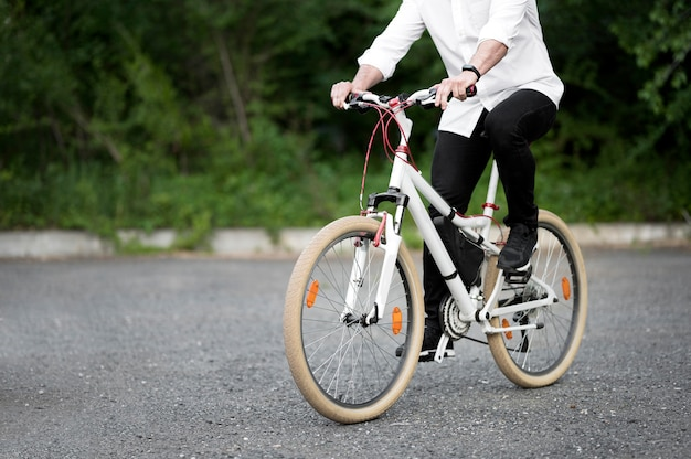Elegant adult male riding bicycle outdoors