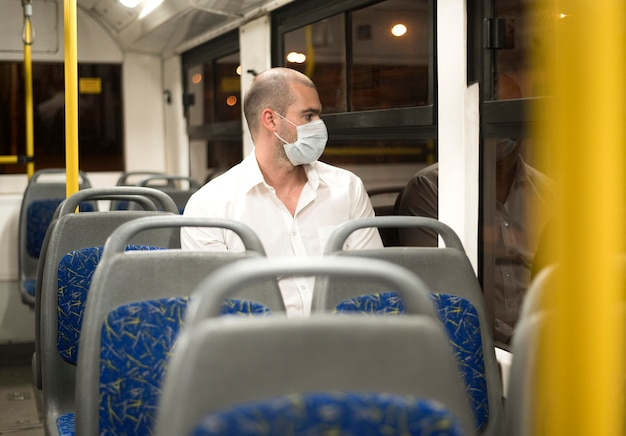 Elegant adult male riding bus with medical mask