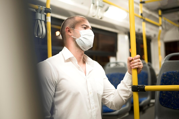 Elegant adult male riding bus with surgical mask