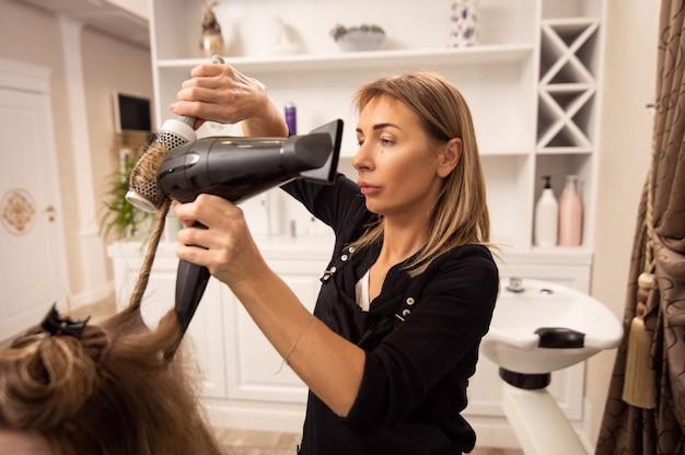 Elegant adult woman hairdresser enjoying working in beauty salon and blowdrying hair of customer
