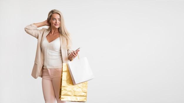 買い物袋を保持しているエレガントな大人の女性
