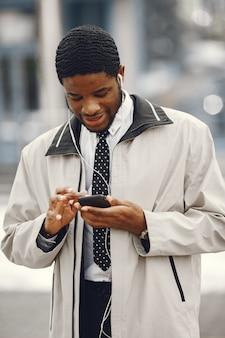 헤드폰으로 휴대 전화를 사용 하여 거리에 서있는 우아한 아프리카 계 미국인 남자.