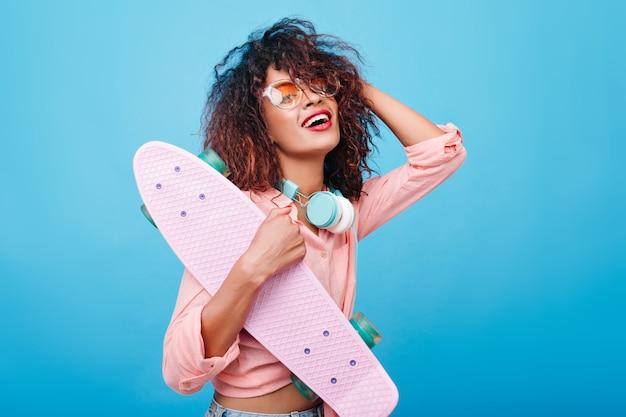 大きなヘッドフォンとスタイリッシュなサングラスを身に着けて、笑顔でピンクのシャツを着たエレガントなアフリカの女の子。スケートボードでポーズをとって巻き毛の髪型を持つ黒人の若い女性の屋内の肖像画。