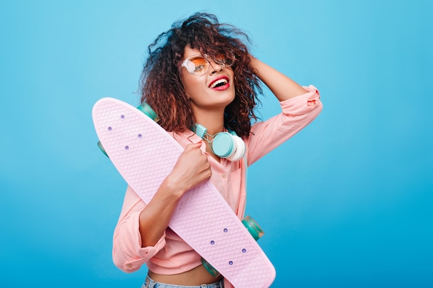 Elegant african girl in pink shirt wearing big headphones and stylish sunglasses, smiling. indoor portrait of black young lady with curly hairstyle posing with skateboard.