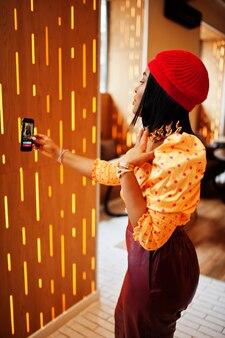빨간 프렌치 베레모, 빅 골드 넥 체인 폴카 도트 블라우스, 가죽 팬츠를 입은 우아한 아프리카 계 미국인 여성이 소셜 네트워크를 위해 휴대폰으로 생방송을 진행합니다.