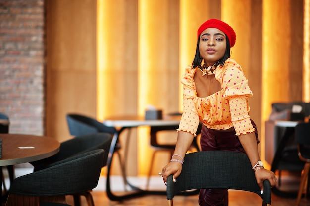 赤いフレンチベレー帽、大きなゴールドのネックチェーンの水玉模様のブラウスと革のズボンのエレガントなアフロアメリカンの女性が屋内でポーズをとります。