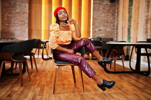 赤いフレンチベレー帽、大きなゴールドのネックチェーンの水玉模様のブラウスと革のズボンのエレガントなアフロアメリカン女性が屋内でポーズ