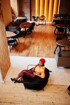 赤いフレンチベレー帽、大きなゴールドのネックチェーンの水玉模様のブラウスと革のズボンのエレガントなアフロアメリカンの女性がプーフに座っています